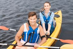 Handsome man enjoying sport activity while rowing in canoe stock images