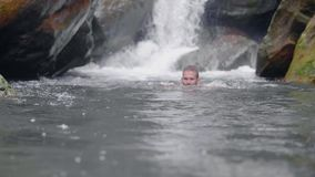 Handsome man enjoying swim in mountain river from tropical waterfall in rainforest. Young man bathing in rocky river on stock footage