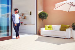 Handsome man enjoys life on rooftop terrace, with open space kitchen and sliding doors Royalty Free Stock Photos