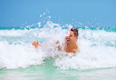 Handsome man enjoys swimming in sea waves. Young handsome man enjoys swimming in sea waves Royalty Free Stock Image