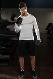 Handsome Man Exercising Biceps With Dumbbells Stock Photo