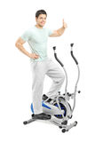 Handsome man exercising on a cross trainer. Handsome young man exercising on a cross trainer and giving a thumb up,  on white Royalty Free Stock Photo