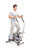 Handsome man exercising on a cross trainer machine. On white Stock Photography