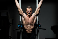 Handsome man exercising his abs at the gym Stock Images