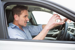 Handsome man experiencing road rage. In his car Royalty Free Stock Photo