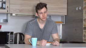 Handsome man falls asleep at the breakfast table in the kitchen.  stock video