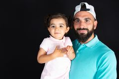 Handsome man fashion style with child daughter in arms on black background. An handsome man fashion style with child daughter in arms on black background royalty free stock photography