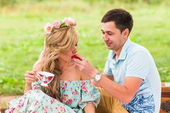 Handsome man is feeding his beautiful woman with a delicious donut in picnic on nature Royalty Free Stock Photography