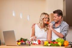 Handsome man feeding woman at kitchen. Royalty Free Stock Photo