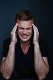 Handsome man feels painful headache. In a black v-neck shirt on a black background Stock Images