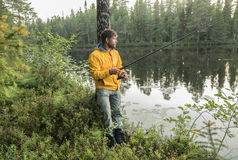 Handsome Man is fishing on the shore of beautiful forest lake Royalty Free Stock Images