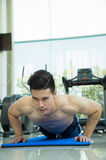 Handsome man fitness exercising by doing push ups as part of bodybuilding training in the fitness center, sport concept Royalty Free Stock Photography