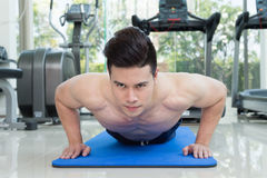 Handsome man fitness exercising by doing push ups as part of bodybuilding training in the fitness center Stock Photo