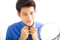 Handsome man fixing his tie in front of mirror Royalty Free Stock Images