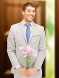 Handsome man with flowers in hand Royalty Free Stock Photography