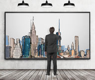 A handsome man in formal clothes is drawing a picture of New York City. Wooden floor, concrete wall and three black ceiling lights Royalty Free Stock Photography