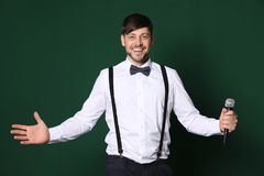 Handsome man in formal clothes posing with microphone royalty free stock photos
