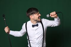 Handsome man in formal clothes singing with microphone stock photo