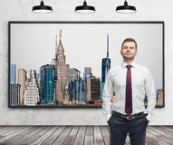 A handsome man in formal clothes stands in front of the picture of New York City on the wall. Wooden floor, concrete wall and three black ceiling lights stock image