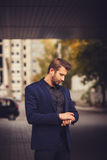 Handsome man in formalwear looking at his watch. I will be in time. Handsome man in formalwear looking at his watch while standing at the street Royalty Free Stock Image