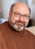 Handsome man in forties portrait. Bearded balding man in forties with light eyes and black glasses grins at camera; black and white; selective focus; 2/3 facial Royalty Free Stock Photos