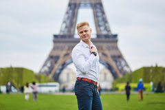 Handsome man in front of the Eiffel tower in Paris, France. Handsome young man in front of the Eiffel tower in Paris, France Royalty Free Stock Photography