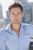 Handsome man frowning at camera on his balcony Stock Image