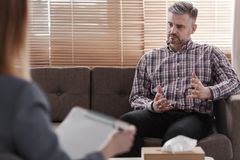 Handsome man gesticulating while talking to his psychologist during a therapy. Handsome men gesticulating while talking to his psychologist during therapy royalty free stock photo