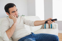 Handsome man getting bored of tv programs Stock Images