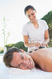 Handsome man getting a hot stone massage poolside Stock Image