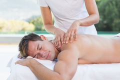 Handsome man getting a massage poolside Stock Image