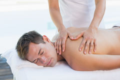 Handsome man getting a massage poolside Royalty Free Stock Photography