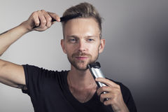 Handsome man gettting ready. Handsome young man combing his hair and trimming his facial hair royalty free stock image