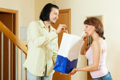 Handsome man gives gift to woman Royalty Free Stock Images