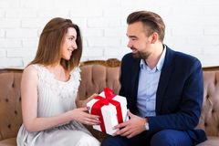 Handsome man giving gift box to his girlfriend Stock Images