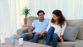 Handsome man giving a gift to his girlfriend. In the living room stock footage