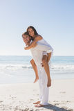 Handsome man giving happy girlfriend a piggy back Stock Images