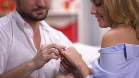 Handsome man giving lady beautiful golden ring on st Valentines day, anniversary. Stock footage stock footage