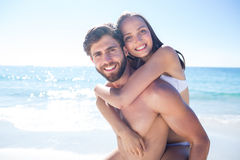 Handsome man giving piggy back to his girlfriend Royalty Free Stock Image