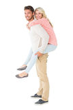 Handsome man giving piggy back to his girlfriend Royalty Free Stock Images