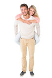 Handsome man giving piggy back to his girlfriend Stock Images