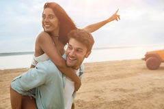 Handsome man giving a piggyback ride to his smiling girlfriend royalty free stock images