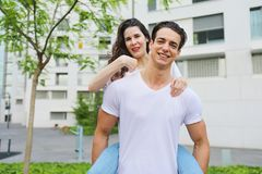 Handsome man giving piggyback to woman stock image