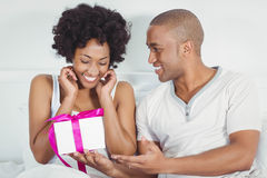Handsome man giving present to his girlfriend. Handsome men giving present to his girlfriend on the bed Royalty Free Stock Image