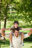 Handsome man giving son a piggyback Royalty Free Stock Photography