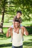 Handsome man giving son a piggyback Royalty Free Stock Photos