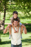 Handsome man giving son a piggyback Stock Photography