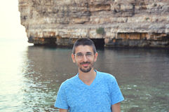 Handsome man with glasess with sea rocky coast background of Polignano a mare, Italy stock images