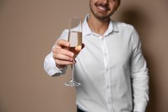 Handsome man with glass of champagne on color background. Closeup royalty free stock photos