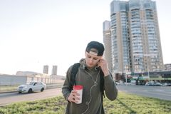 A handsome man with a glass of hot drink in his hands listens to music and corrects headphones in his ears against the backdrop of. Urban scenery. Life styles Royalty Free Stock Images